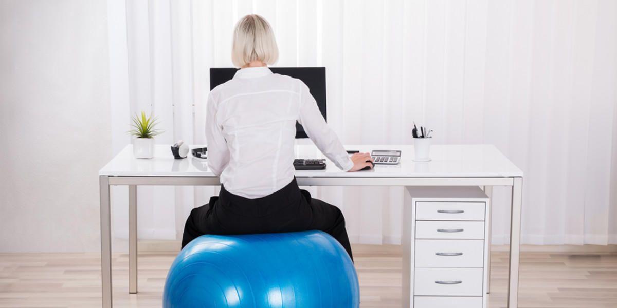 Frau sitzt am Schreibtisch auf einem Gymnastikball.