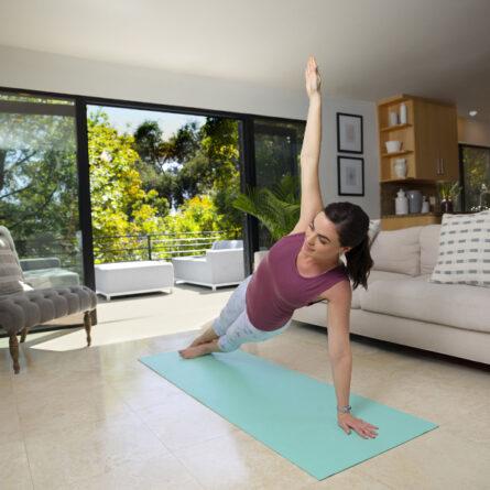 Frau mit Garmin-Uhr macht Fitnessübungen auf eine Yogamatte