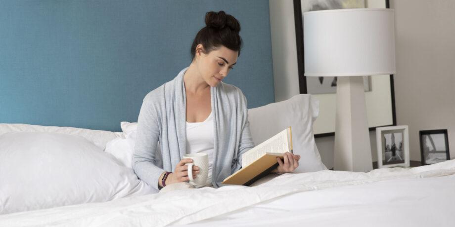 Frau mit Garmin-Uhr sitzt mit einem Kaffee im Bett und liest ein Buch